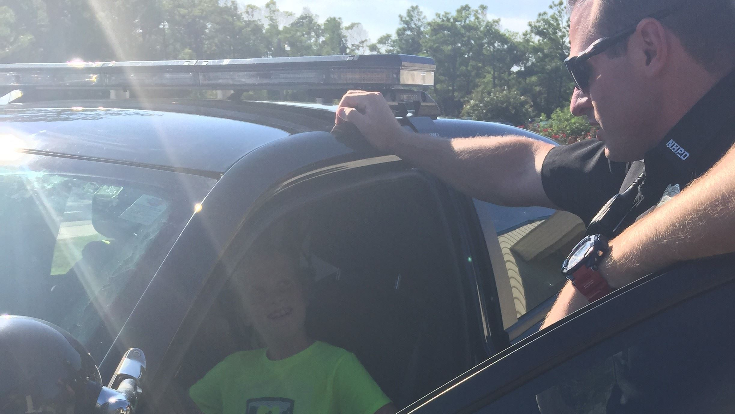 Officer talking to kid in car