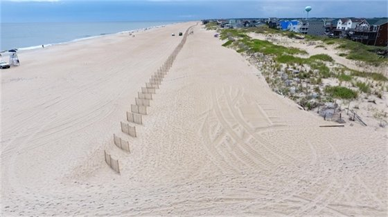 Sand fencing and sea oats being placed on Nags Head's newly nourished beach in south Nags Head on August 16, 2019.